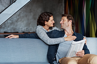 Buy stock photo Shot of a smiling woman hugging her husband from behind while sitting on a sofa in their living room