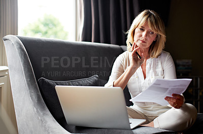 Buy stock photo Shot of a mature woman working on a laptop and reading paperwork in her living room