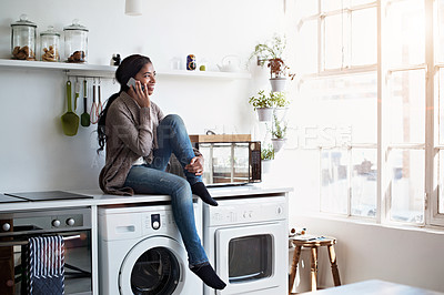 Buy stock photo Shot of a young woman sitting on her kitchen counter talking on the phone