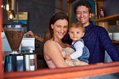 Buy stock photo Portrait of smiling couple and their little girl standing in the window of their bakery