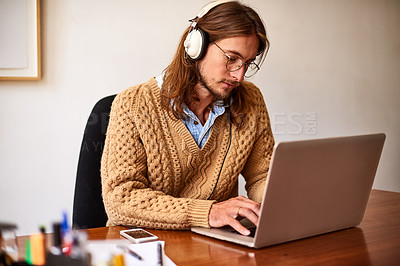 Buy stock photo Shot of a young designer working on a laptop and listening to music on headphones in an office
