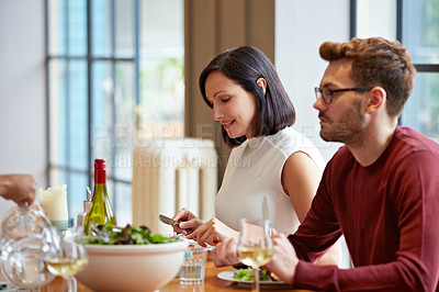 Buy stock photo Sho tofa young couple listening to conversation over dinner at home