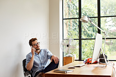 Buy stock photo Shot of a young man using his cellphone while working in his home office