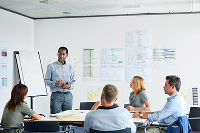 Buy stock photo Shot of a man giving a presentation to coworkers in an office