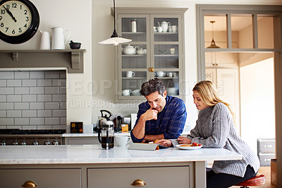 Buy stock photo Shot of a young couple using a digital tablet while sitting at their kitchen table at home
