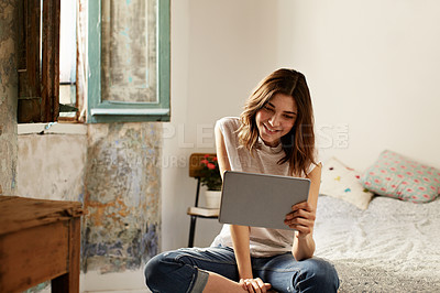 Buy stock photo Shot of a young woman using a digital tablet while sitting on her bed