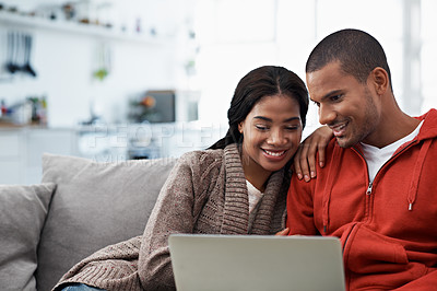 Buy stock photo Shot of a smiling young couple sitting on their sofa using a laptop