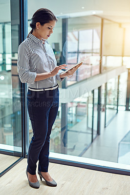 Buy stock photo Shot of a young businesswoman working on a digital tablet in an office