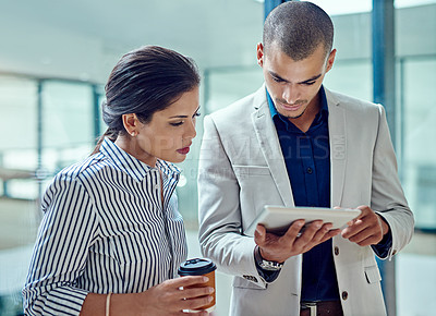 Buy stock photo Cropped shot of two businesspeople working together on a digital tablet in an office