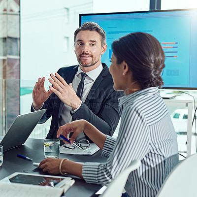 Buy stock photo Shot of two businesspeople having a meeting in the boardroom