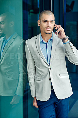 Buy stock photo Shot of a young businessman using his phone at work
