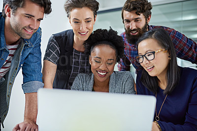 Buy stock photo Cropped shot of colleagues working together on a laptop in a modern office