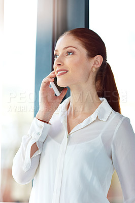 Buy stock photo Shot of a thoughtful young businesswoman talking on the phone while looking out of her office window