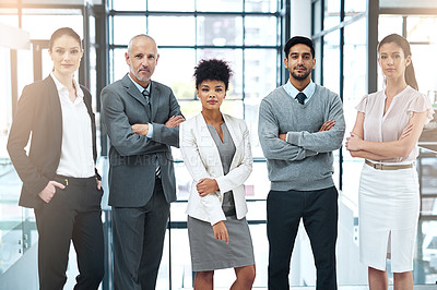 Buy stock photo Portrait of a focused group of colleagues standing together in a modern office