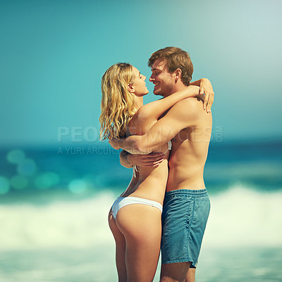 Buy stock photo Cropped shot of an affectionate young couple embracing on the beach