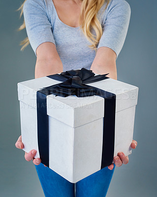 Buy stock photo Cropped studio shot of a young woman holding out a present wrapped with a bow