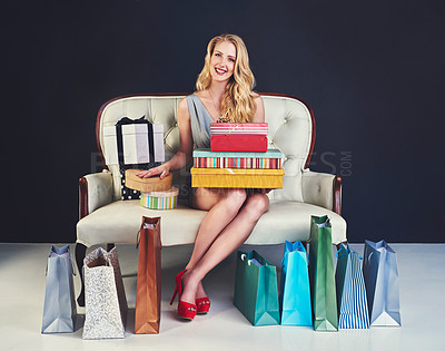 Buy stock photo Studio shot of a young woman sitting on a couch surrounded by gifts