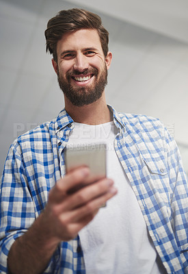Buy stock photo Portrait of a young designer using a cellphone in a modern office