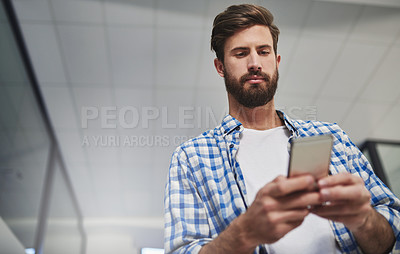 Buy stock photo Cropped shot of a young designer using a cellphone in a modern office