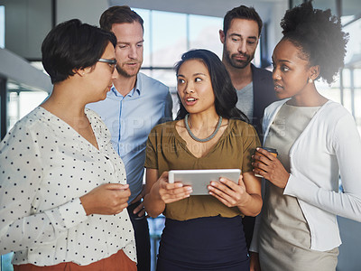 Buy stock photo Cropped shot of a group of businesspeople looking at a tablet in the office