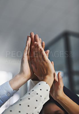 Buy stock photo Low angle shot of a group of unrecognizable coworkers high fiving in the office