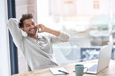 Buy stock photo Shot of a young entrepreneur speaking on his cellphone in his office