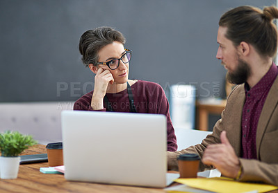 Buy stock photo Cropped shot of a bored businesswoman listening to her colleague explain something