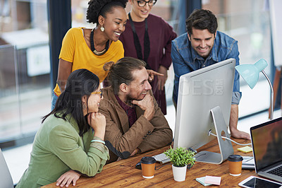 Buy stock photo Cropped shot of a group of creative businesspeople looking at something on a computer