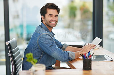 Buy stock photo Cropped shot of a creative businessman working on his tablet at his desk