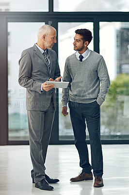 Buy stock photo Full length shot of two businessmen looking at a digital tablet in their office