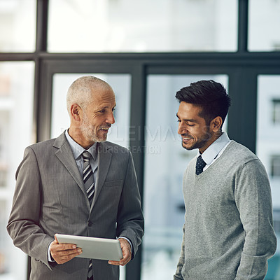 Buy stock photo Cropped shot of two businessmen looking at a digital tablet in their office