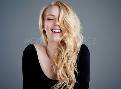 Buy stock photo Studio portrait of an attractive young woman with beautiful long blonde hair laughing against a gray background