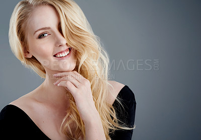 Buy stock photo Studio portrait of an attractive young woman with beautiful long blonde hair posing against a gray background