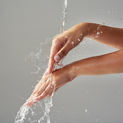 Buy stock photo Cropped shot of hands held out under a stream of water against a grey background