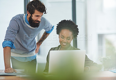 Buy stock photo Shot of two creative businesspeople looking at something on a laptop