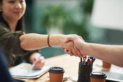 Buy stock photo Cropped shot of two creative businesspeople shaking hands over the table
