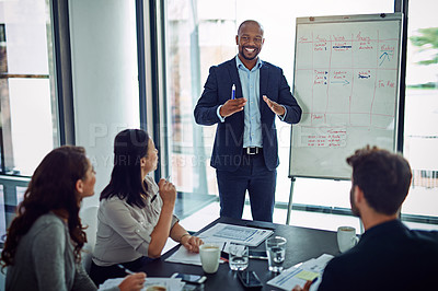 Buy stock photo A businessman giving a presentation to coworkers in the boardroom