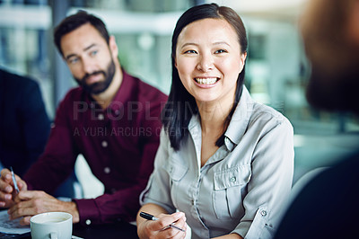 Buy stock photo Shot of a businesswoman in a meeting with her colleagues blurred out