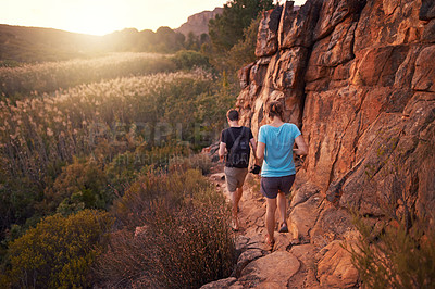 Buy stock photo Full length shot of a young couple hiking in the mountains