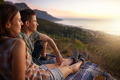 Buy stock photo Shot of a young couple watching the sunset together outdoors
