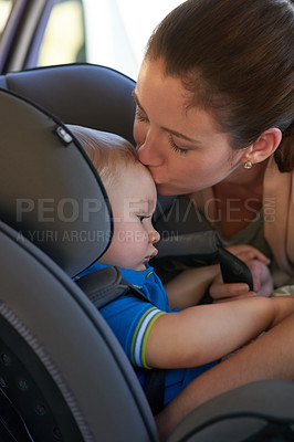 Buy stock photo Cropped shot of a mother kissing her baby boy sitting in a car seat