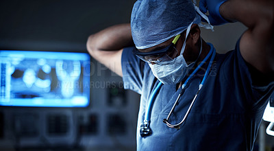Buy stock photo Shot of a surgeon putting on his surgical mask in preparation for a surgery