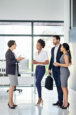 Buy stock photo Full length shot of a group of businesspeople talking in the office