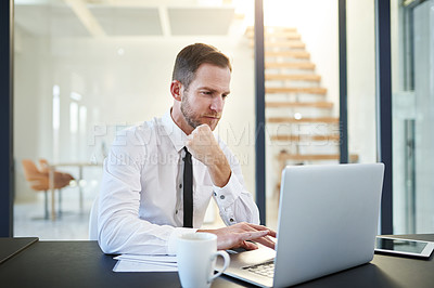 Buy stock photo Cropped shot of a businessman working on a laptop in a modern office