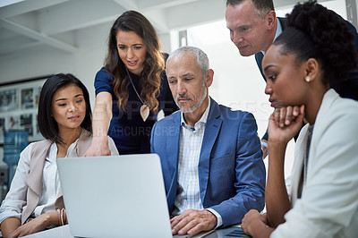 Buy stock photo Cropped shot of businesspeople working together on a laptop in a modern office