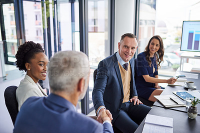 Buy stock photo Cropped shot of businesspeople shaking hands during a boardroom meeting