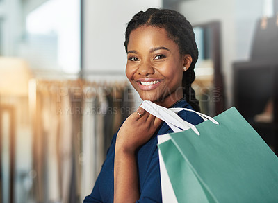 Buy stock photo Cropped shot of a young woman smiling and holding a shopping bag in a store