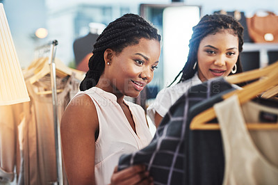 Buy stock photo Cropped shot of two women looking at clothes on a rail in a store