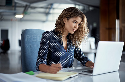Buy stock photo Cropped shot of a young businesswoman making notes while working on a laptop in a modern office