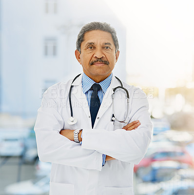 Buy stock photo Portrait of a confident and mature doctor folding his arms